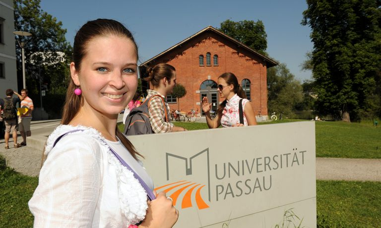 Female student in front of the stele with the university logo