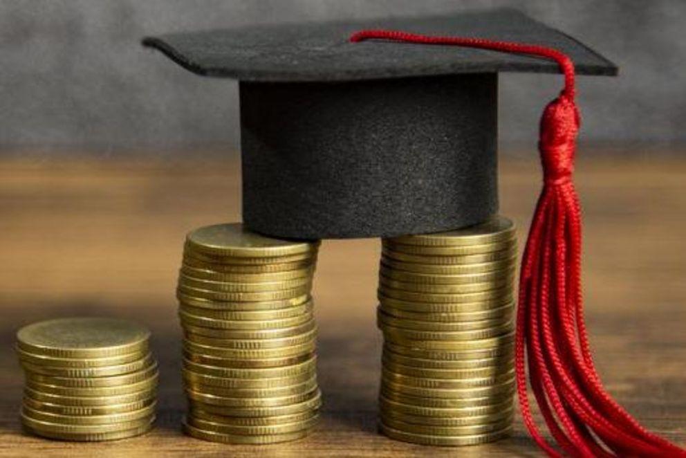 ein Absolventenhut steht auf mehreren Münzstapeln
